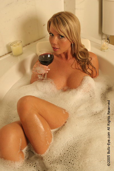 Nikki sips wine in the bathtub