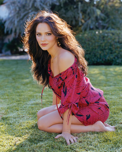 Katharine McPhee kneeling on the grass in a red dress