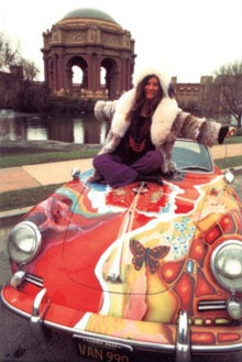 Janis Joplin sitting on a car