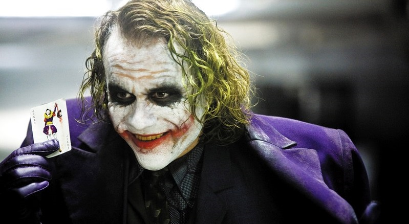 Heath Ledger as The Joker holding playing cards