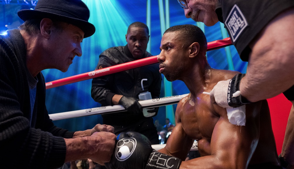 Michael B Jordan as Adonis Johnson in Creed 2 sitting in ring corner talking to Rocky Balboa