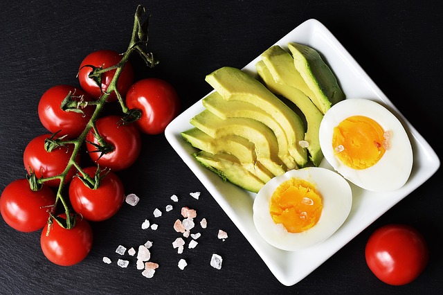 sliced avocados hard boiled eggs and vegetables on plate