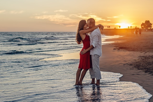 man and woman kissing on the beach with sunset in background