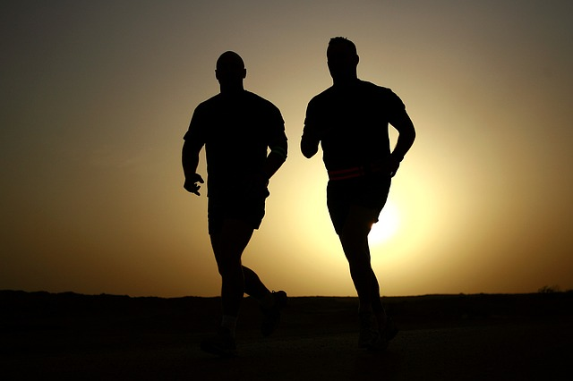 men jogging with sunrise behind them