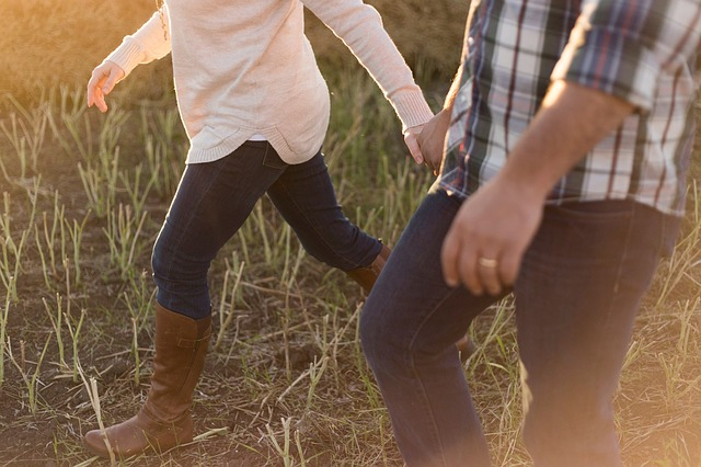 couple holding hands walking through grass
