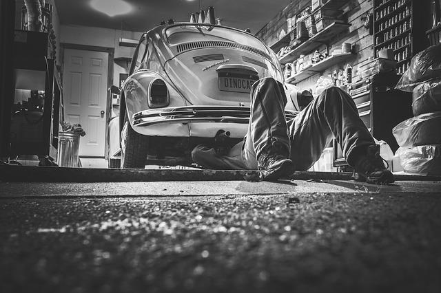 man repairing an old car