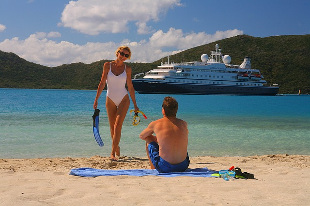 woman in swimsuit with cruise ship behind her