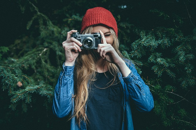 pretty female hipster with camera taking photo
