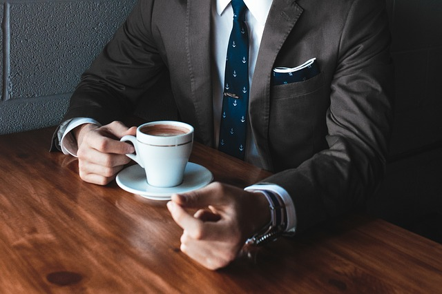 man in business suit drinking coffee